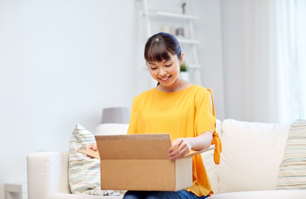 people, delivery, commerce, shipping and shopping concept - happy asian young woman with cardboard parcel box at home